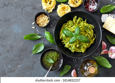 Pasta tagliatelle with pesto sauce and fresh basil leaves in black bowl. Top view with copy space.
