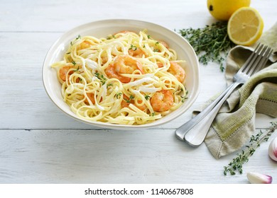 Pasta tagliatelle with shrimps in creamy sauce. White slats background. Top view