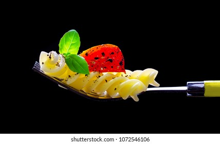 Pasta, tomato and basil on a fork, isolated against a black background