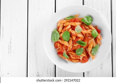 Pasta with tomato sauce and basil on wooden table close up
