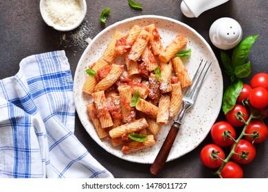 Pasta with tomato sauce and basil. Pasta tartilloni on a dark background.