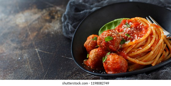 Pasta with tomato sauce and meatballs on a dark background