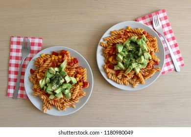 Pasta with tomato sauce, red peppers, corn and avocado. Two plates, top view.