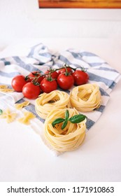 Pasta with tomatoes and fresh basil leaves on a white background. Assorted pasta with cherry tomatoes on a cloth. Copy space.