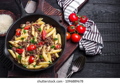 Pasta with tomatoes and meat on  dark rustic background.Selective focus.
