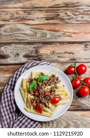 Pasta with tomatoes and meat on wooden rustic background. Top view.