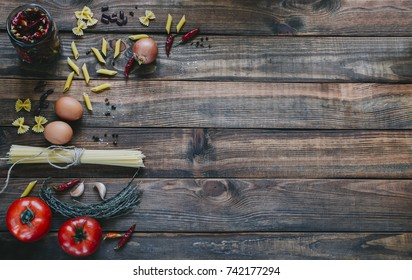 Pasta and tomatoes on wooden rustic background, recipe concept