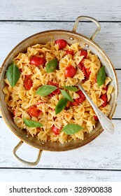 pasta with tomatoes in pan, food top view