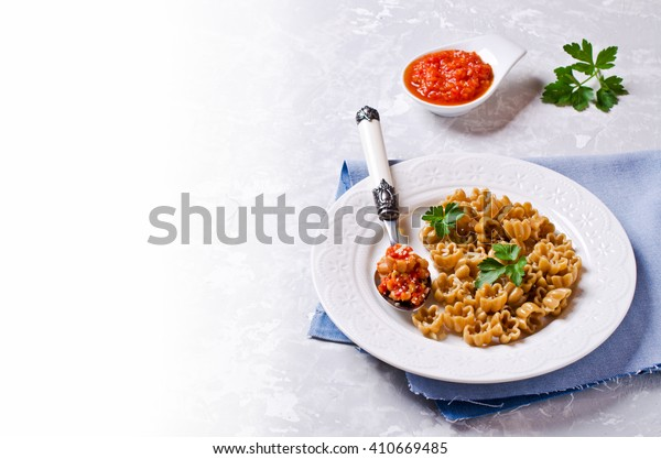 Pasta with vegetable sauce on bright concrete background. Selective focus.