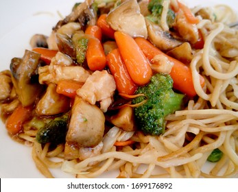 Pasta with vegetables, mushrooms and chicken on a white plate. Chinese pasta,fried soba noodles with mushrooms, carrots, peppers closeup on white plate