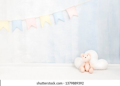 Pastel baby background in soft light blue and pink colors with teddy bear cloud toy figure near paint wall in child room. Newborn concept greeting card. Place for text