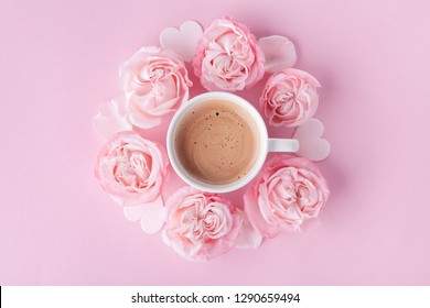 Pastel background with morning cup of coffee and beautiful rose flowers. Cozy breakfast for Womens day. Flat lay.