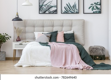 Pastel bedsheets on bed with beige bedhead in woman's bedroom interior with leaves posters on the wall and vase on white nightstand
