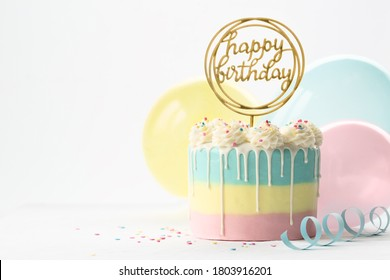 Pastel birthday cake with drip icing and balloons