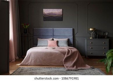 Pastel blanket on bed in pink and blue bedroom interior with gold lamp on grey cabinet