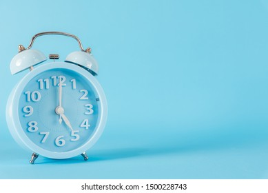 Pastel blue alarm clock with five o'clock on blue background. 5 am, 5 pm. Time concept.