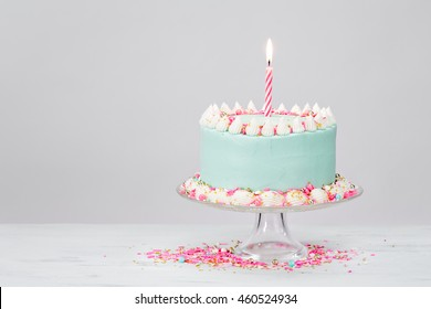 Pastel Blue Birthday Cake with Pink Sprinkles over White Background.