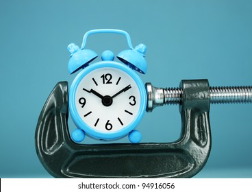 A pastel blue colored  alarm clock placed in a Grey clamp against a pastel blue background, asking the question do you manage your time effectively.