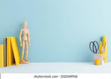 Pastel blue mock up young student desk, with yellow supples, mannequin, notebook and copy space.