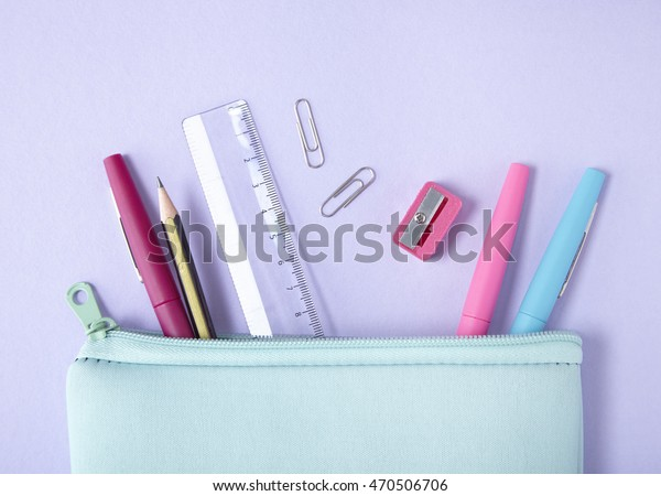 A pastel blue pencil case with stationery and pens spilling out on to a purple background