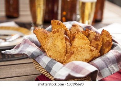 Pastel, a Brazilian snack, with a bar in the background.