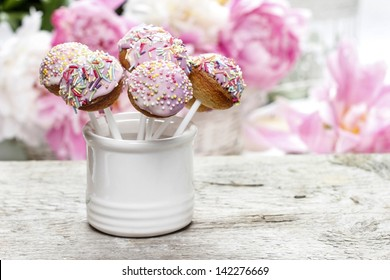 Pastel cake pops on rustic wooden table. Stunning peony flowers in the background.