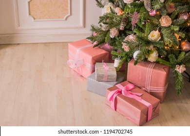 Pastel christmas.Elegant christmas tree with decorations and gifts on elegant hardwood floor. Pink Christmas gift boxes with pink and silver ribbon next to decorated Christmas tree. Candy pink,soft