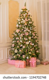 pastel christmaselegant christmas tree with decorations and gifts on elegant hardwood floor pink