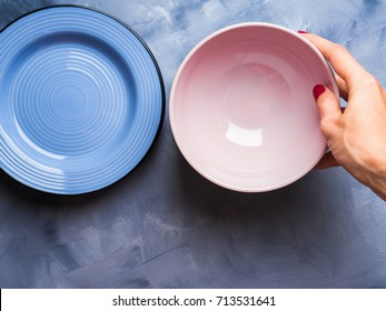 Pastel color plate and bowl with woman's hand holding it