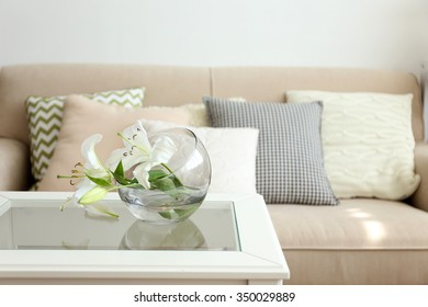 Pastel color sofa with beautiful pillows and vase with flowers on the table in front of it in the room