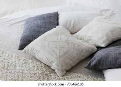Pastel color, white and light grey cushions or pillows setting on bed with satin bedding style.
