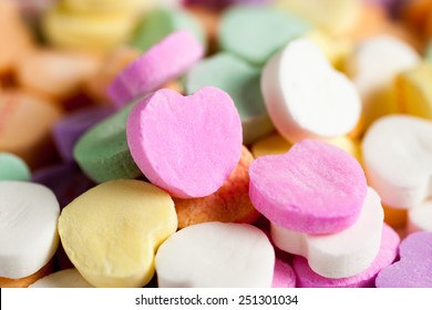 Pastel colored candy hearts in a pile on a white surface.