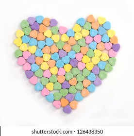 Pastel colored candy hearts in the shape of a heart isolated on white
