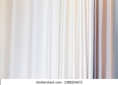 Pastel colored curtains on window. Textile folds of drapery.