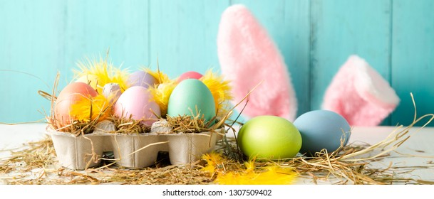 Pastel colored easter eggs in a egg box with hay and feathers as a nest and rabbit ears behind against a wooden turquoise background. Banner size