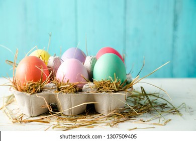Pastel colored easter eggs in a egg box with hay as a nest against a wooden turquoise background