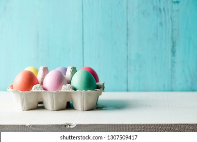 Pastel colored easter eggs in a egg box with a wooden turquoise background