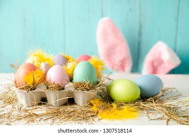 Pastel colored easter eggs in a egg box with hay and feathers as a nest and rabbit ears behind against a wooden turquoise background