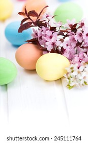 Pastel colored Easter eggs next to blooming branch