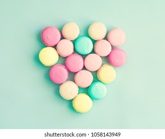 Pastel colored french macaroons over mint background