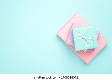 Pastel colored gift boxes on turquoise background. Minimal styled flat lay for Mother's Day, Birthday and Holiday. Books wrapped in gift paper.