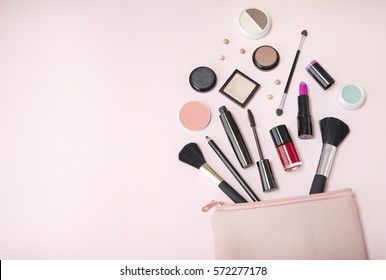 A pastel colored make up bag with beauty products spilling out on to a pale pink background, with empty space at side