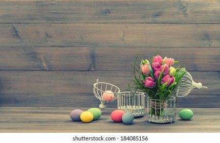 pastel colored tulip flowers and easter eggs over wooden background