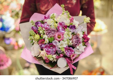 Pastel colors bouquet made of orchids, Freesia, Carnation and Limonium flowers in hands