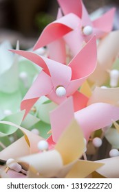 Pastel coloured wind toys in a bucket.