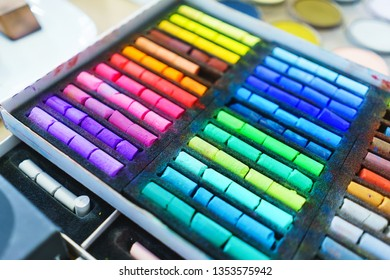 Pastel crayons paint special box. Accessories for painting with pastels. Small pieces of crayons top view. Concept school of art and drawing training. Soft focus.