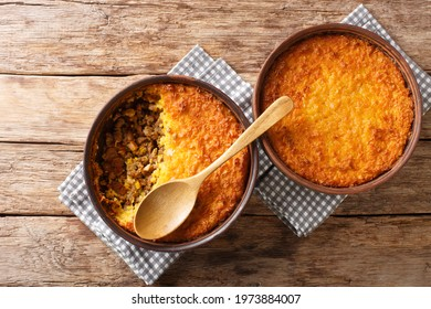 Pastel de choclo corn pie is a Chilean dish based on sweetcorn and beef closeup in the pots on the table. Horizontal top view from above