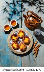 Pastel de Nata Frisch gebackene portugiesische Eierspeise Tee und Tee auf blauem Holztisch