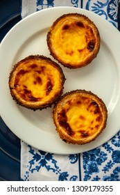 Pastel de Nata On A Blue Plate With Traditional Blue And White Azulejo Tile Towel Background