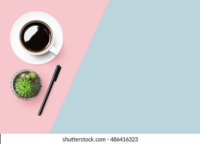 Pastel desk table with coffee and pen. Top view with copy space, flat lay.